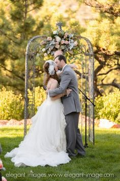 First Kiss under the Pewter Ceremony Arch Adorned with Fleur De Lis at Lionscrest Private Mountain Venue. Weddings at Lionscrest Manor, Lyons, Colorado.