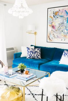 Add interest to a white-walled living room with a blue velvet cot, crystal chandelier, statement art and a plug-in wall lamp
