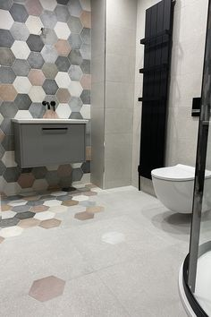 Create a truly unique bathroom by mixing coloured hexagon tiles on a feature wall which runs down onto the floor. Pair with a black radiator, taps and shower for a creative and modern interior space. Tile For Small Bathroom, Bathroom Wall Tiles, Black Bathroom Taps, Hexagon Tile Bathroom, Bathroom Feature Wall, Tiled Bathrooms, Hexagon Tiles, Upstairs Bathrooms, Bathroom Layout