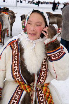 Valla, a Nenets woman, using a mobile phone. Yamal, Northwest Siberia, Russia.