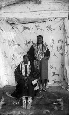 She Came Spotted and an unidentified Native American Sioux woman, posed outside on a fur skin rug in front of a painted backdrop of a Lakota style Indian war record, Pine Ridge Agency, South Dakota -...