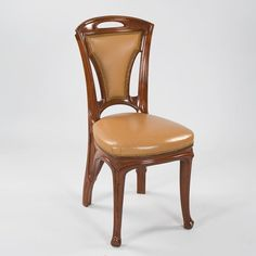 A French Art Nouveau side chair by Vallin with mahogany carvings and leather upholstery.