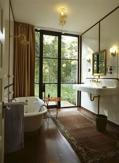 Glass House, East Hampton Photo: Chris Bausch Sign of the Crab faucet, Vintage farmhouse porcelain sink, Vintage clawfoot tub, Tord Boontje Garland brass pendant light, Enameled board with mahogany details, Piero Fornasetti tray table.