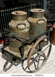 Photo about Old wheelbarrow carrying two old milk cans. Image of farm, barn, jugs - 2517375 Antique Milk Can, Vintage Milk Can, Vintage Farm, Vintage Antiques, Antique Tools, Old Milk Cans, Milk Jugs, Milk Bottles, Painted Milk Cans