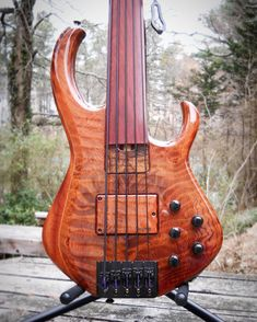 """Skjold - Figured Redwood Fretless 5"