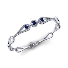 This glistening Halo Sapphire Bracelet captures the eye.Crafted, by Jewelry Designs, from White Gold. Our bracelet features 3 sapphires totaling ct. as well as ct of fine diamond accents. Sapphire Bracelet, Sapphire Jewelry, Link Bracelets, Jewelry Bracelets, Halo, Jewelry Design, White Gold, Jewels, Eye