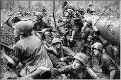 Vietnam War, 1966 - American infantrymen crowd into a mud-filled bomb crater (photo by Henri Huet)