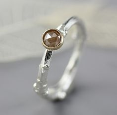 """""""Twig Ring with Rose Cut Diamond"""" Created by Sarah Hood One of a Kind A lovely sterling silver ring cast from a real lilac twig is the perfect backdrop for a blush-colored rose cut diamond. The diamond is set simply in a 14k yellow gold bezel setting. Diamond: natural, untreated rose cut, 4.5mm, .40 carat. All of my diamonds are ethically sourced, and purchased from reputable sellers who do not buy or trade in conflict diamonds. This ring can be sized to fit you at no charge between sizes…"""