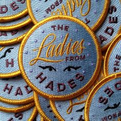 The Ladies from Hades iron-on full embroidered patch  Light periwinkle purple background, yellow, and a dark grey mauve are the main colours. Patch