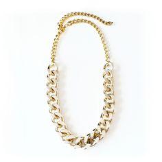 Collar de cadena metálica de eslabones gruesos en tono dorado y con un acabado pulido.  Podés usarlo bien ajustada alrededor del cuello de una camisa o usarlo más suelto con una musculosa amplia con escote en V o redondo.
