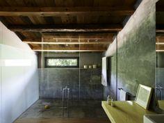 #reforma #baño en casa rural rehabilitada, zona de ducha con cerramiento de vidrio y suelo de microcemento, zona de baño con lavabo sobre encimera de madera y suelo de parquet.