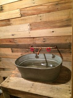 Rustic vessel sink with copper piping In bathroom with pallet walls.