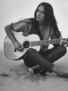 Joan Baez playing guitar on the beach before her set at the Newport Folk Festival in 1959