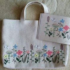 """『樋口愉美子のアップリケ刺しゅう』の""""Field Flowers""""を娘のレッスンバッグに。あー可愛いです、この図案 力つきて両面に刺繍できず、裏面は花畑からさまよいでたミツバチと、真ん中に娘の学校の校章をアップリケ…。 裏地は、花園感が似てると思ってリバティのIrmaにしてみた #樋口愉美子 #yumikohiguchi #樋口愉美子のアップリケ刺しゅう #リバティ #liberty #irma #checkandstripe #レッスンバッグ #刺繍 #刺しゅう #stitch #embroidery #handembroidery"""