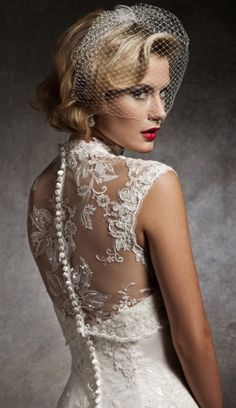 Vintage wedding bridal makeup with red lips and a veil that compliments the details of the wedding gown.