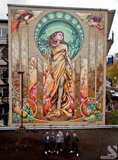 """Cinco artistas de Montreal, criaram um mural gigantesco em um prédio de 5 andares inspirado na obra """"Our Lady of Grace"""" do pintor art nouveau Alphonse Mucha. A obra, inspirada no estilo floreado, em que se destacam as formas orgânicas inspiradas em folhagens e flores do pintor tcheco, essa arte foi feita em 16 dias seguidos, faz parte de um projeto do coletivo que pretende espalhar grandes murais com intuito de colorir um pouco as cidades."""