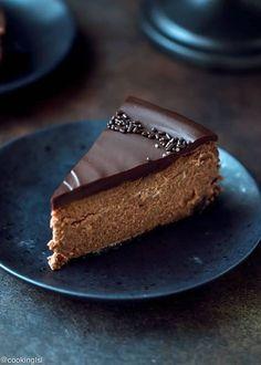 Chocolate Mascarpone Cheesecake Recipe. A slice of chocolate cheesecake topped with thick chocolate ganache. The perfect slice on a black plate.