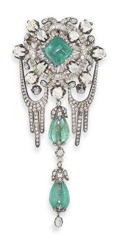 An emerald and diamond corsage ornament, possibly Russian, second half of the 19th century. The sugarloaf emerald set at the centre within a cartouche frame of cushion-shaped, old brilliant and rose-cut diamonds, suspending rose-cut diamond tasselled swags and a central drop composed of two polished emerald beads and old brilliant and rose-cut diamond foliate motifs, mounted in silver and gold