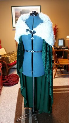 Winter Warrior Fur Cloak  ---------------------  This cloak made with flowing, dark green suede fabric is perfect for your next snowy adventure. The overlay is made with faux yak fur and fastened around the neck by a durable, pleather, antler tip buckle. This cape design was made originally for the premiere of Thor 2 where I went as Lady Loki. It was looked fantastic, was comfortable, and warm! It would work well as an elf cloak, warrior cloak, or King or Queen! When ordering:  >No comments…