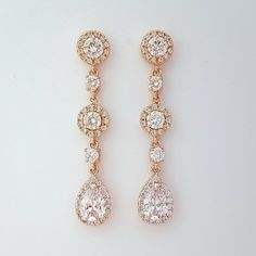 Elegant long Cubic Zirconia tear drops are set in an open setting in rose gold plated brass bezel and surrounded by tiny cubic zirconia crystals. They dangle from Cubic Zirconia detailed round posts with rose gold plated brass settings and are interspersed with two sizes of cubic zirconia connectors. # length of Earring from top of Ear wire is approx 2.4 inches or 6 cms Matching necklace https://www.etsy.com/listing/200509487/rose-gold-necklace-wedding-necklace Bra...
