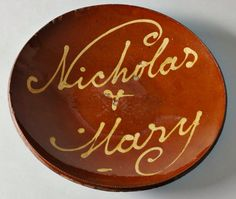 """Skinner's - The Personal Collection of Lewis Scranton, Auction 2897M. May 21, 2016. Lot: 238.  Estimate: $1,500-3,000.  Realized: $4,250.   Description:  Large Redware Plate with Yellow Slip Inscription """"Nicholas & Mary,"""" Norwalk, Connecticut, early 19th century, round, with coggled rim, (minor rim chips and glaze loss), dia. 14 1/2 in.   Provenance: Yankee Smuggler, 1993."""