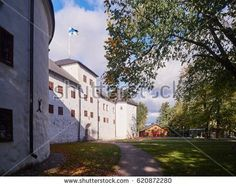 Stock Photo: Turku castle in bright sunshine in Finland with the finnish flag on a sunny summer day. -