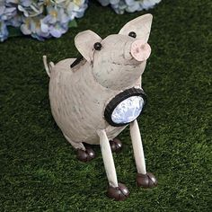 "Charming Solar Pig, Item #47063, $9.99    Our adorable pig sculpture will light up at dusk with a blue LED in a faceted lens at his collar. Skillfully crafted of sheet metal and antiqued with a blush undertone, this little guy will add a bit of country personality to your patio or garden. Solar panel recharges in the sun, complete with an on-off switch. Measures 12"" long x 9½"" tall x 3"" wide."