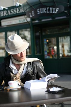 Man reading a book, drinking coffee, with a cat and a hat. But it isn't Dr. Seuss.