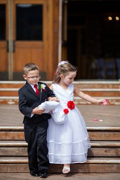 Flower girl + ring bearer outfit idea - ring bearer in black suit + red tie and flower girl in white dress with red flowers {Ashley Kidder, Wedding Photographer}