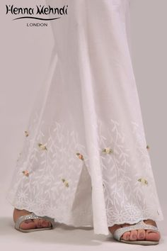 White cotton trousers with flower embellishment. Please note these are trousers only. Please note delivery time is approximately weeks. There is no excha Pajama Pants Pattern, Kurti Styles, Mix Match Outfits, Mehndi Style, Diy Clothes, Clothes For Women, Salwar Designs, Silk Pants, Indian Outfits