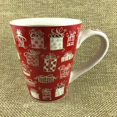 Has assorted gifts all over the exterior surface and a red ribbon running down the handle. Starbucks Christmas Mugs, Starbucks Mugs, Christmas Gifts, Christmas Decorations, Red Mug, Red Arrow, Red Ribbon, 3 Things, Tableware