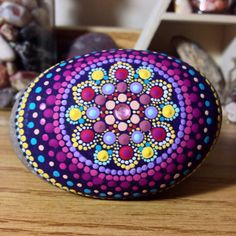 This hand-painted stone is from the shores of Scots Bay, Nova Scotia. Home to some of the worlds highest tides along the Bay of fundy. It has since been transformed into a colourful little treasure. This oval shaped stone measures about 9cm x 6cm x 3cm. It has been painted using acrylic paints and sprayed with 3+ coats of an acrylic gloss finish. It also has a small jewel stuck to the centre icon. The jewel is fixed in place using a dab of glue and is easily removable. (White paint…