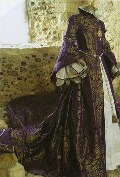 Replica of Mary Tudor's wedding dress.  Mary's dress was recorded in one contemporary report to be in the French style & made of rich tissue w/a border & wide sleeves, embroidered upon purple satin, set with pearls of our store, lined with purple taffeta'. It had a partlet, the sleeveless jacket covering just the chest & a high collar. The kirtle was of white satin enriched with silver and it had a train.  The replica was made for the 450th anniversary of Mary and Philip's wedding in…