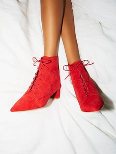 Victorian-inspired suede lace-up ankle boots featuring a pointed toe and block heel. This chic style is easily dressed up or down.