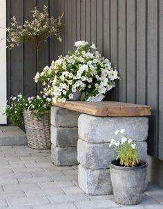 Gartenbank aus großen Steinen und einem Holzbrett