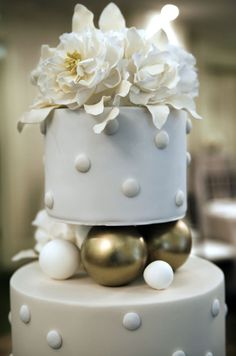 White and gold balls, sugar peonies and white polka dots give this cake a modern twist. #WeddingCake