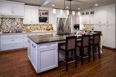 Tie a dark island into a lighter kitchen with a multi-colored tile backsplash that picks up both hues.