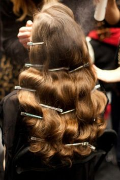 Creating an old 1940s old hollywood waves. After styling and brushing out the hair.. Place the section clips to secure the curls and set with hairspray. To keep up with time you can work on the face and apply makeup.