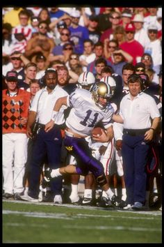 Quarterback Mark Brunell of the Washington Huskies runs down the sidelines during a game against the Arizona Wildcats at Arizona Stadium in Tucson...