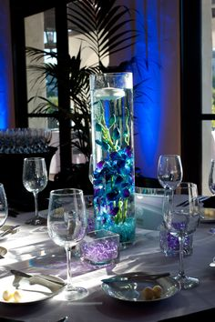 inexpensive and pretty centerpieces.. pick a flower that matches your wedding colors(i used blue orchid), submerge in water and add floating candle. for a little extra, surround with colored gel beads and led light
