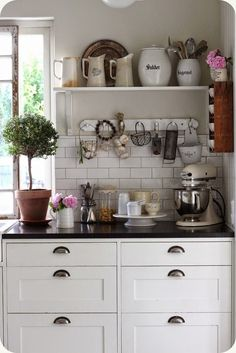 Love the black counter over the white cabinets. Great vintage details