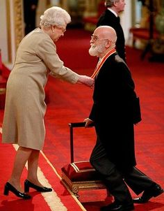 Terry Pratchett being knighted by the Queen Of England.  He is now SIR Terry.