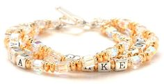 Gold Swaroski Mommy Bracelet designed with 14k gold filled saucer beads, sterling silver spacers and Swarvoski cube crystals to represent the birthstones of each child.  A name can be spelled out in sterling silver alphabet beads on each strand.  This mommy name bracelet is pictured in clear crystals but can be ordered with a different color crystal on each strand for each child's birth month.