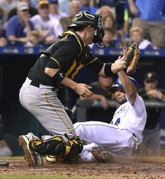 Kansas City Royals' Omar Infante (14) scores before the tag from Pittsburgh Pirates catcher Chris Stewart (19) in the seventh inning on a bunt by Jarrod Dyson during Wednesday's baseball game on July 22, 2015 at Kauffman Stadium in Kansas City, MO.