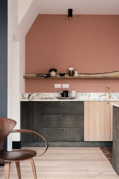 peachy pink walls with marble countertops and rustic black and tan wood cabinets. / sfgirlbybay