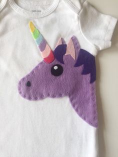 What is more magical and unique then a unicorn? Your little girl will sparkle in our handmade onesie/bodysuit/toddler shirt. .HANDCRAFTED.  Every design I make is unique and handmade by me! Once you have chosen your desired colors, I hand stitch your custom design onto a high quality 100% cotton bodysuit/onesie. A lining is added on the inside of the item to preserve the stitching and protect babys skin.  .ONESIE/SHIRT CARE INSTRUCTIONS.  The felt we use for our appliques is environmentally…