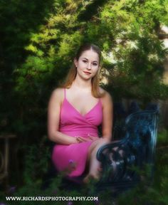 Sitting on a wrought iron bench wearing a pink dress looking very relaxed. Senior portrait taken in San Antonio.