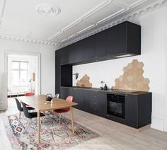 white wall black cabinet black appliances flat panel cabinet wooden table black bar stool red black stool light wood floor heptagon shaped wall feature area rug of Irresistible Kitchen with Black Appliances Ideas