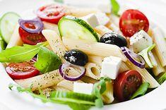 Salát z vařených těstovin, cherry rajčat, listů bylinek, okurky, balkánského sýra a oliv, servírovaný přelitý dresinkem.