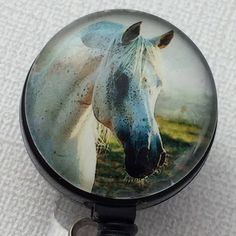 This retractable ID badge reel features a white horse with black markings. The badge has a glass dome over the horse picture. ID Badge reels are stylish and practical. They are a great accessory for H